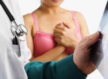 Doctor examine xray slide with nervous woman on pink bra waiting on background